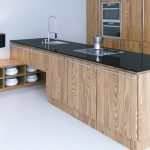 Kitchen island with wooden cabinets and black worktop