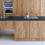 Modern kitchen with wooden cabinets and black quartz worktop