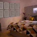 Bedroom with upholstered headboard and pink flower frames