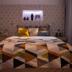 Double bed with pink upholstered headboard and colourful patchwork