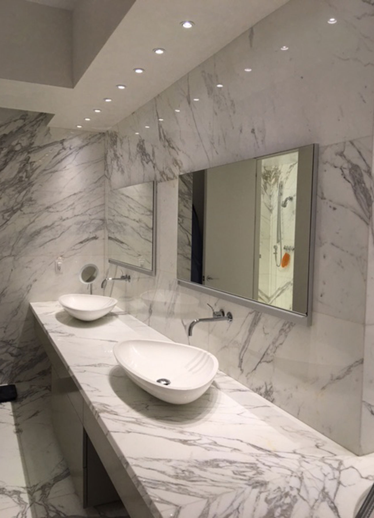 All-marble bathroom with two sinks and mirrors