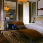 Modern hotel room featuring chaise longue and desk