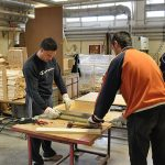 Team working on wooden pieces for construction site