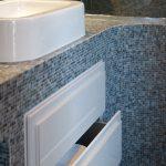 Storage solution in blue mosaic bathroom